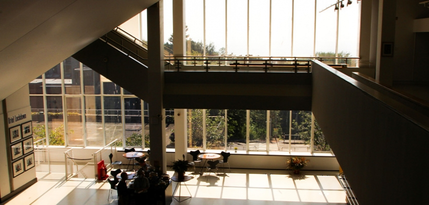 A photo of the inside of the Arts Centre, showing the cafe area and the big glass windows