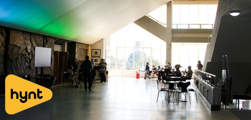 A photo of the Arts Centre foyer, with people milling around on a shiny floor with a colourful ceiling above them
