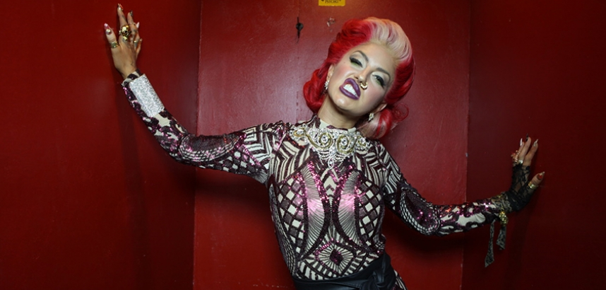 Neon Hitch leans against a red wall in a sequinned dress