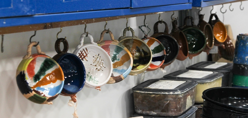 A row of handmade pottery bowls, hanging from a shelf inside the pottery studio
