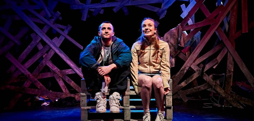 A man and a woman sat on a wooden create, on a stage inside a theatre.