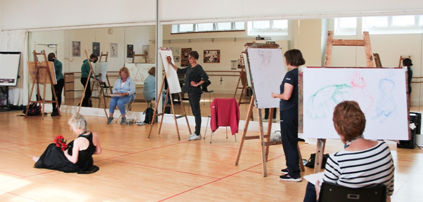A drawing class taking place inside a dance studio, where everyone is drawing a woman dancing in the middle of the floor