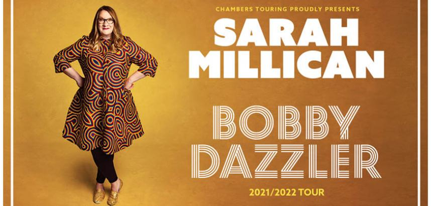 A full-body promotional shot of Sarah - she stands, wearing a colourful dress, with her hands on her hips. The background is a deep mustard colour. Her name and show title also appear in large letters.