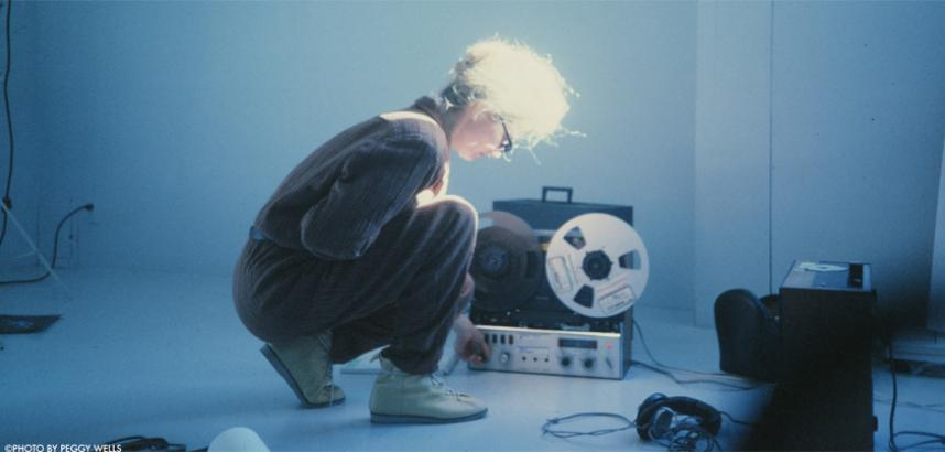 Woman knelt down operating a reel to reel tape recorder.