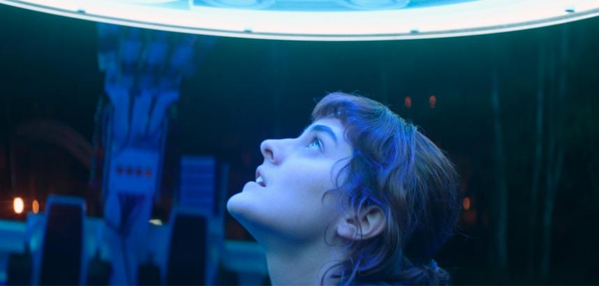 A lady looking up at fairground ride lights