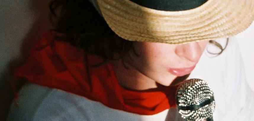 A close-up of a person in a straw hat, partially obscuring their face, a red scarf, and a white t-shirt. They're holding a microphone and appear to be reading something out of frame.