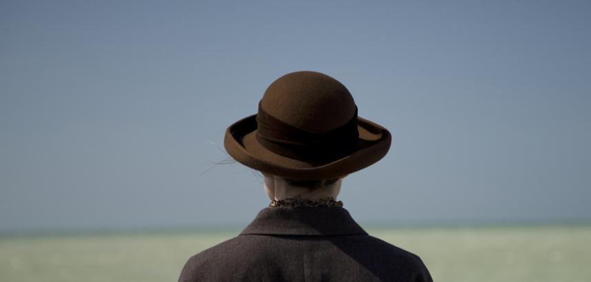 The head and shoulders of a person wearing a round, brown hat. Their back is to the camera, and they look toward a blue sky and a green sea, the horizon splitting the image in two.