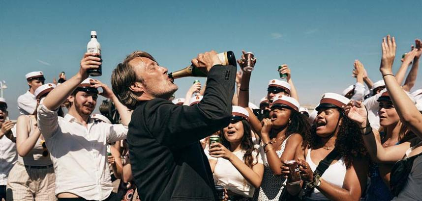 Movie Poster fo Another Round showing Mads Mikkelsen downing a bottle of beer in front of a crowd