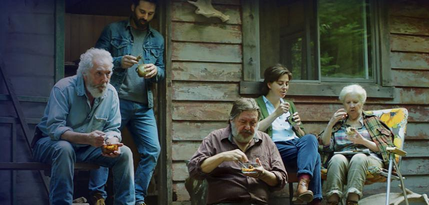 five people sitting outside on a porch