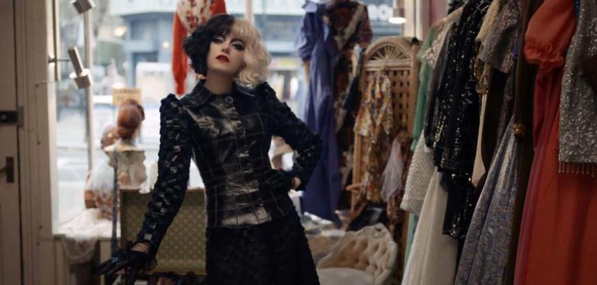 Emma Stone as a young Cruella stands in a Womenswear shop
