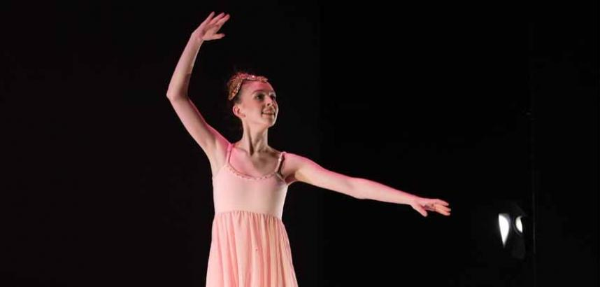A young ballet dancer, wearing pink, on stage.