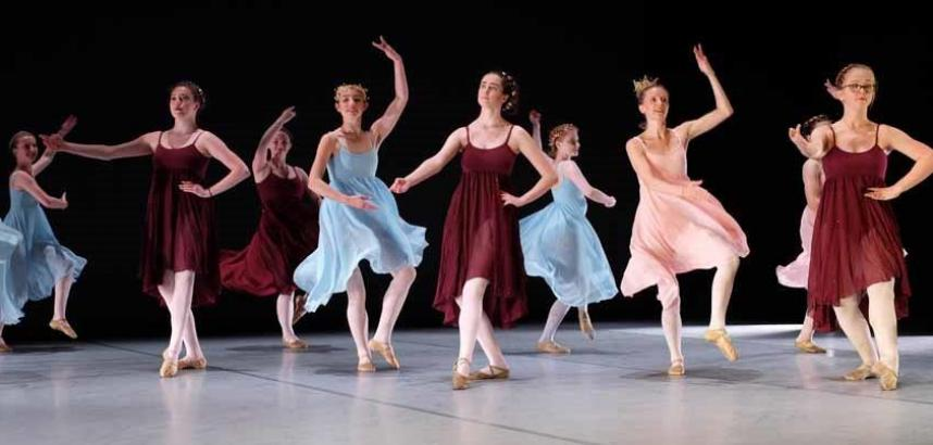 A row of young ballet dancers on stage.