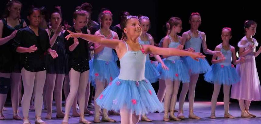 A row of young ballet dancers on stage, wearing shades of blue.
