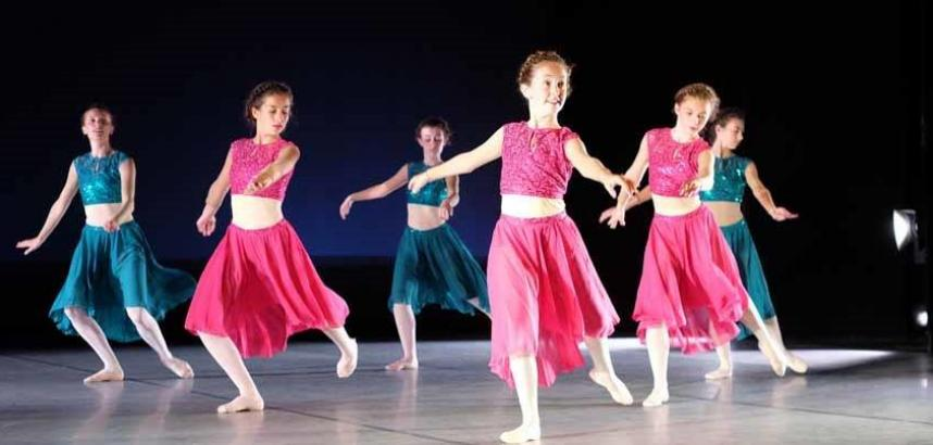 A number of young ballet dancers on stage in pink and turquoise outfits.