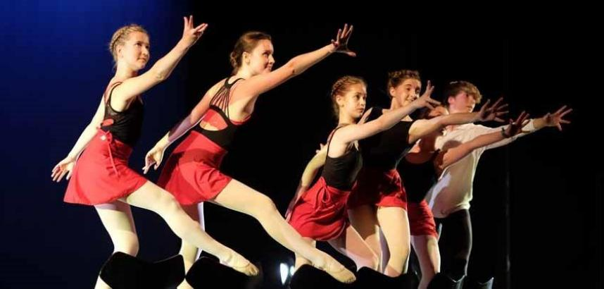 A row of red-clad dancers, mid-move, on stage.