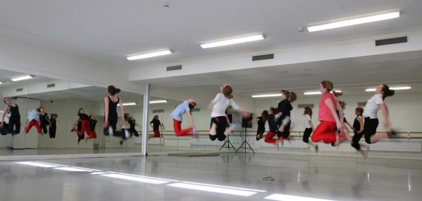 A class of young people are mid-jump in a mirrored dance studio.