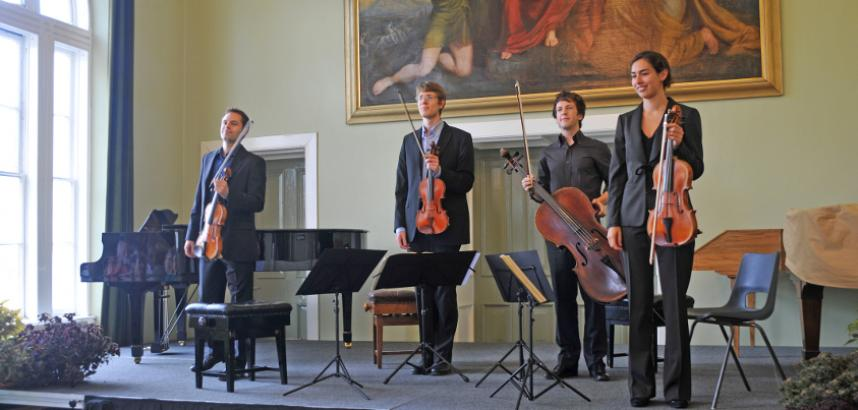 A string quartet stands on a stage, a grand painting hanging on the wall behind them.