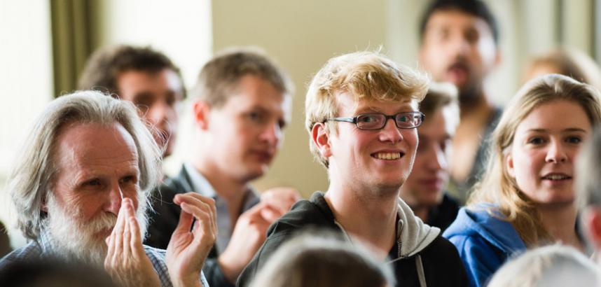 An audience of people, some blurry, and at centre a young man wearing glasses smiles at the camera. | Cynulleidfa o bobl, rhai'n aneglur, ac yn eu canol dyn ifanc sy'n gwisgo sbectol ac yn gwenu i'r camera.