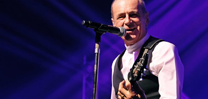 Francis Rossi at the mic, holding a guitar, on stage. He's wearing a black waistcoat.