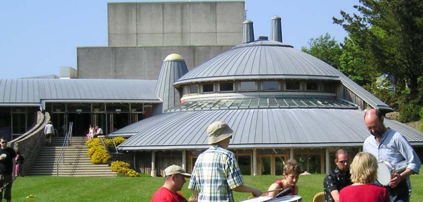 A generic image of outside the Arts Centre's round pottery studio, with people milling around in the foreground.