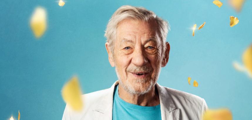 A medium-distance photo of Sir Ian McKellen against a blue background. Sir Ian wears a white jacket and a blue t-shirt with the number 80 on it. | Llun o Syr Ian McKellen ar gefndir glas. Mae Syr Ian yn gwisgo siaced gwyn a chrys-t glas gyda'r rhif '80' ar y blaen.