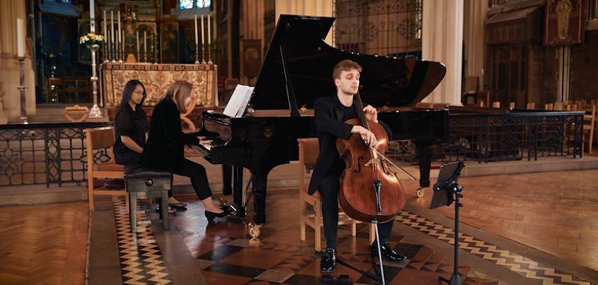 Leo Popplewell plays cello while Antonina Suhanova sits playing a piano