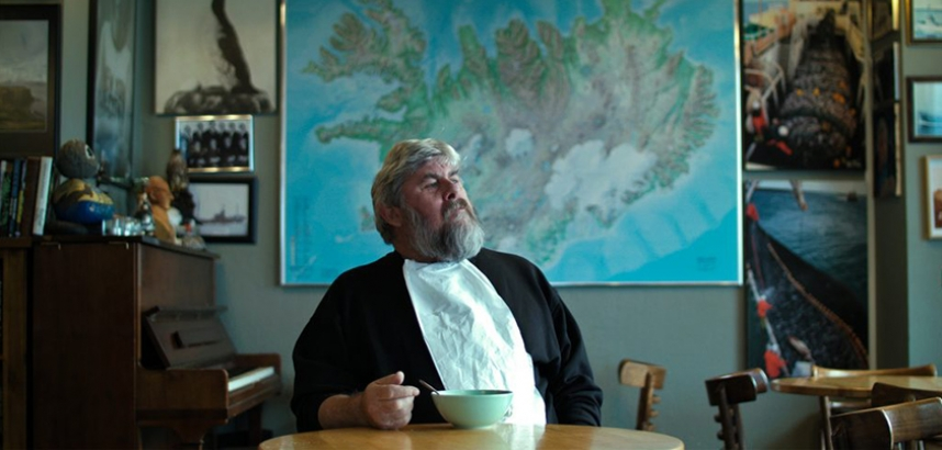 Still from Lobster Soup showing an old man eating soup in front of a map of Iceland