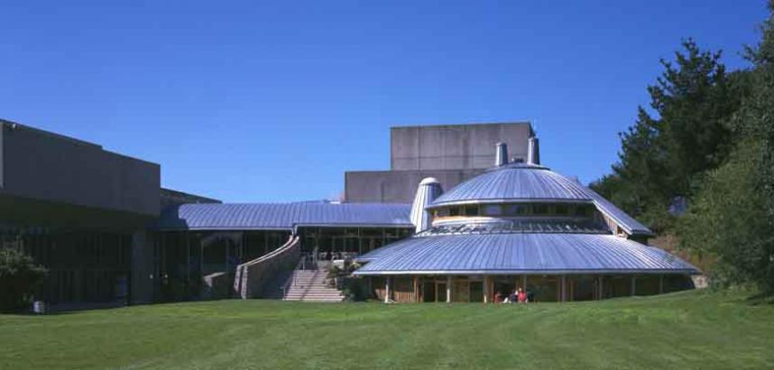 A long view of the Arts Centre, taken from the grassy Chapel Court. The Great Hall is visible at the left, as well as the main building entrance and the round extension that includes the pottery studio and performance studio.