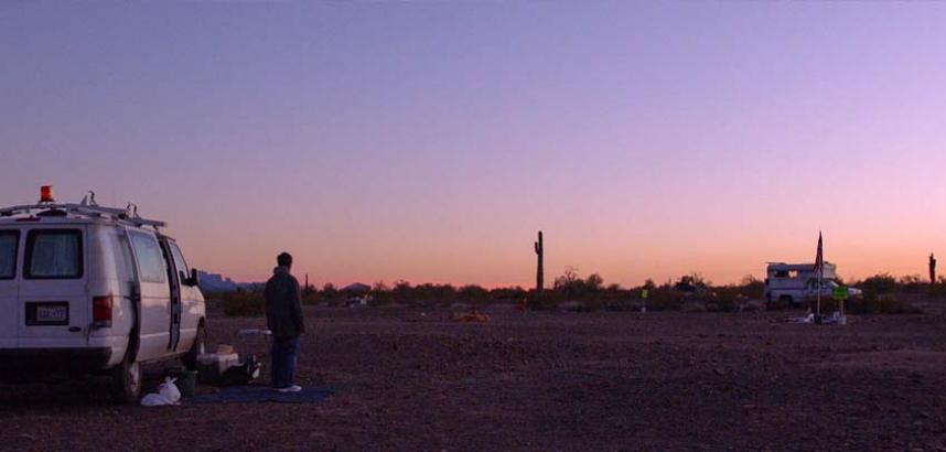 A campervan is parked in an American desert landscape