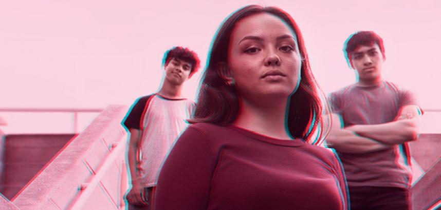 A teenage girl stands looking into the camera with two boys stood behind her with their arms folded