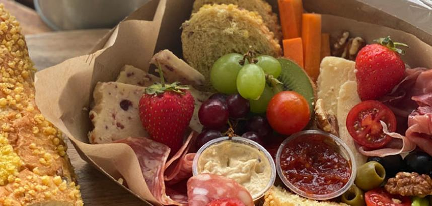A close-up of a mezze box, filled with fruit, vegetables, meats, olives and more.