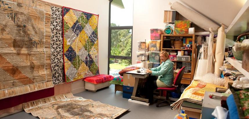 A long shot of a textile artist's studio. The artist sits at a table, with lots of shelving behind. A large textile piece hangs on the wall.