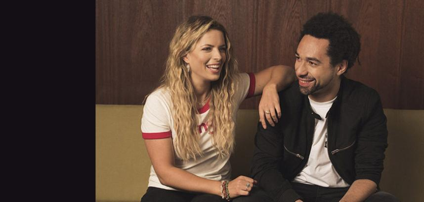 A promotional image of The Shires, a duo, who are are laughing together and dressed casually.