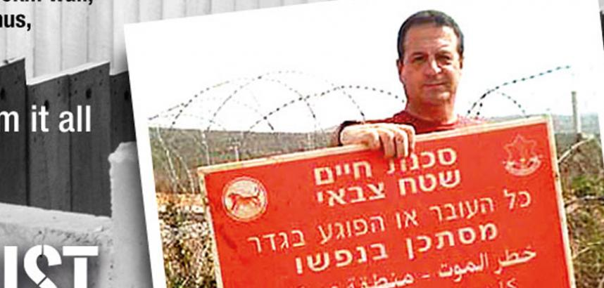 Mark Thomas holds a red and white sign which features text in Hebrew and Arabic. There is barbed wire behind him.