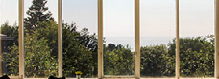 A photo of the windows of the Arts Centre, facing out over the trees, sea and sky