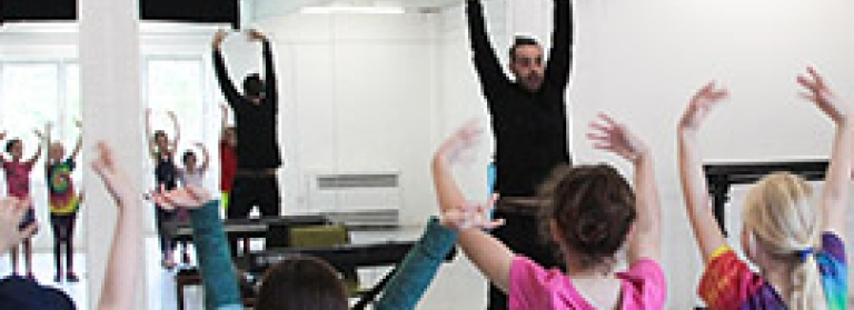 A music and drama teacher leading children in an acting exercise