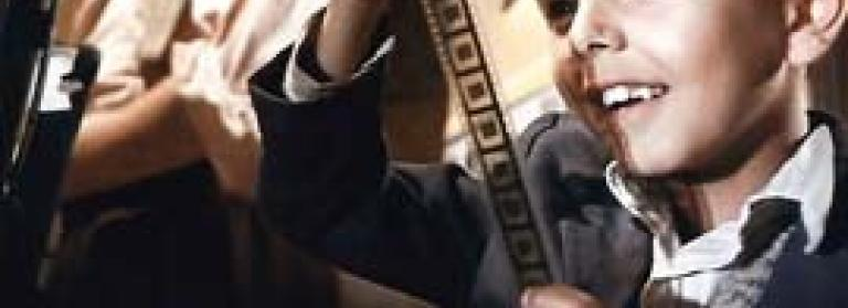 A boy looks in delight at a reel of film - text reads Cinema Paradiso