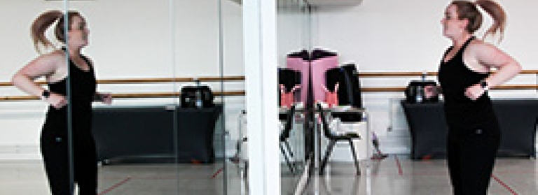 A dance teacher demonstrating a dance move, facing her reflection in the dance studio mirrors