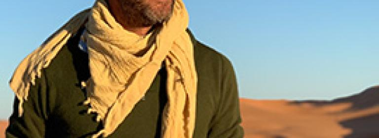 Ben Fogle standing side-on, a dramatic desert landscape behind him. He's wearing a green top and a yellow scarf.