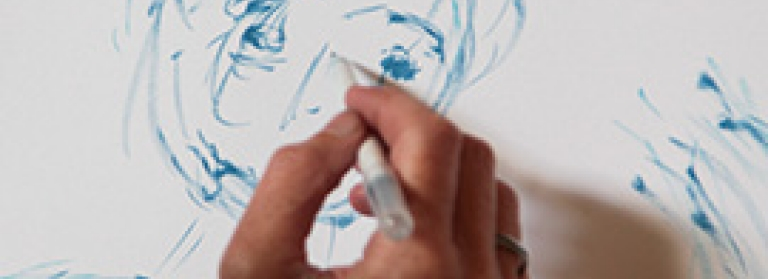 A person's hand holding a blue felt pen, loosely sketching a face onto a piece of paper