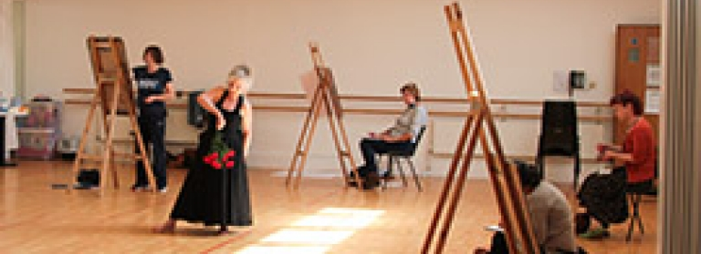 A drawing class inside a dance studio, with everyone working at easels, drawing a woman who is posing in the middle of the room