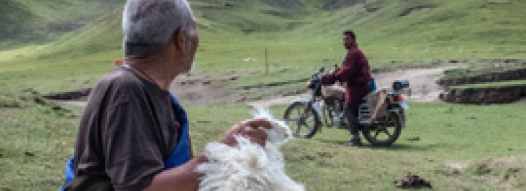 A Tibetan man holds a sheep and talks to another man on a motorcycle