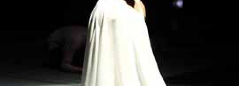 A kneeling dancer performer, dressed in white on a dark stage.