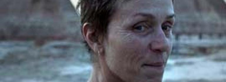 Francis McDormand stands on a rocky shore gazing into the camera