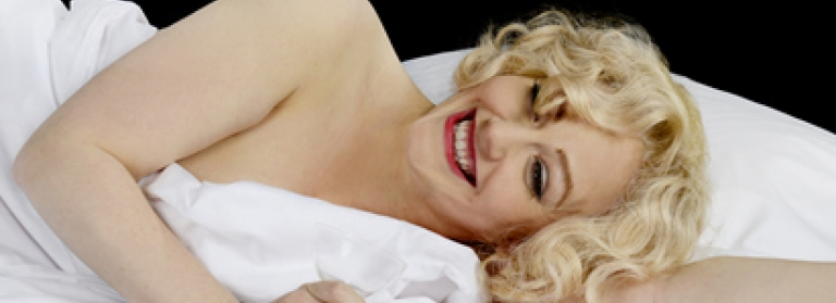 An actress playing Marilyn Monroe lies down in white bedsheets