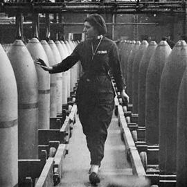 Woman inspecting rows of bombs in a factory.