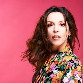 Close up of Bridget Christie looking into the camera lens, against a pink background