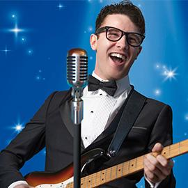 A photograph of a man dressed as Buddy Holly, smiling while playing an electric guitar. There is a microphone in front of him.
