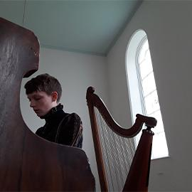 Cerys Havana sat playing the piano in a white room, with a harp behind her