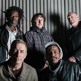 Five men, the members of Dreadzone, framed tightly and looking straight to camera, with a shadowy background.